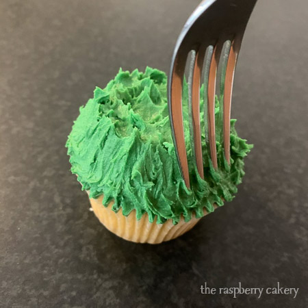 Step 2 - use your fork to create grass texture around the outside of the buttercream. (Easter Bunny Cupcakes Tutorial)